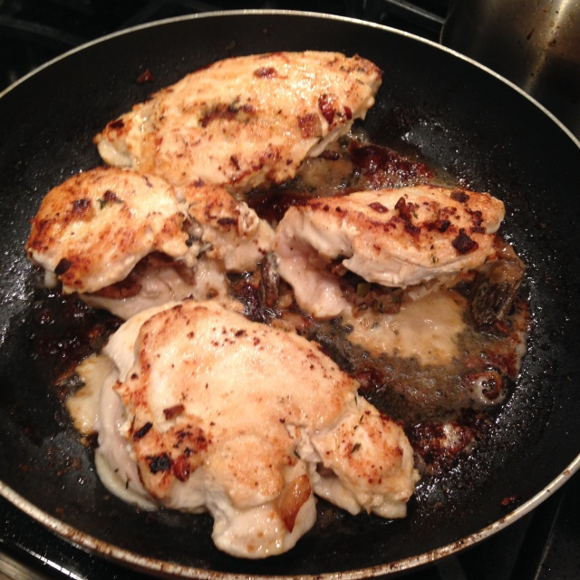 Chicken cooking in the skillet. Notice the morels and chanterelles inside the folded-over chicken