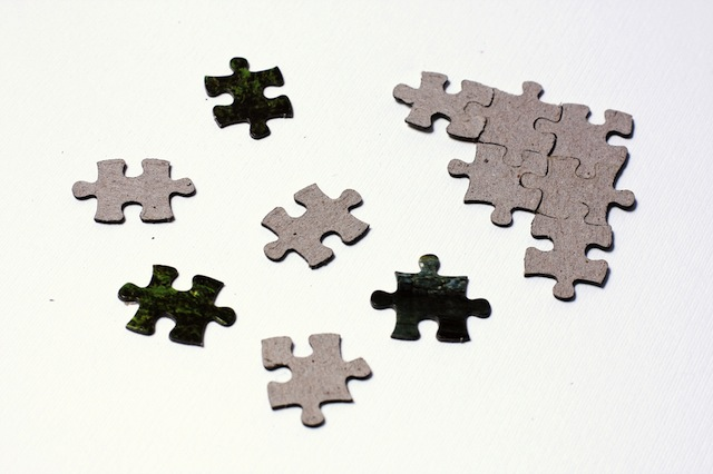 Several jigsaw puzzle pieces scattered on a white surface. Some are with the face up while others are with the face down. On the right upper corner there is a partially solved fragment made out of six pieces.