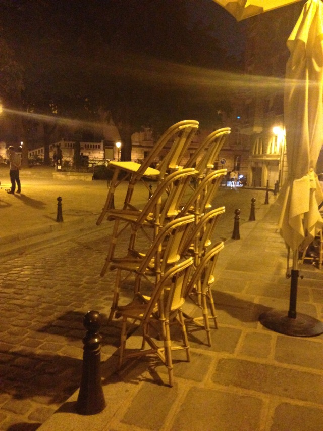 Paris. Place Dauphine. Restaurant Paul. Cchairs stacked up because its almost closing time