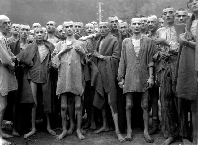 """Starved prisoners, nearly dead from hunger, pose in concentration camp in Ebensee, Austria.  The camp was reputedly used for """"scientific"""" experiments.  It was liberated by the 80th Division.  May 7, 1945.  Lt. A. E. Samuelson.  (Army) NARA FILE #:  111-SC-204480 WAR & CONFLICT BOOK #:  1103"""