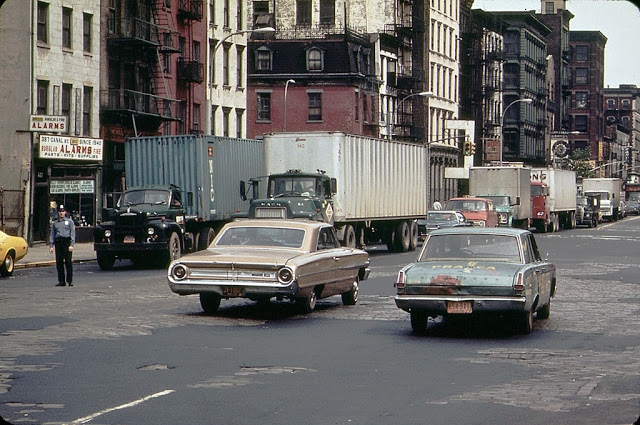 A-1960s-Ford-Galaxie-and-a-battered-early-1960s-Plymouth-Valiant-cruise-along-Canal-Street-with-peeling-pavement